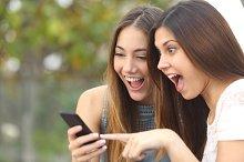 Euphoric friends watching videos on a smartphone.jpg