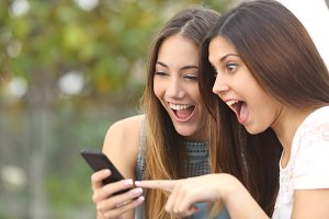 Euphoric friends watching videos on a smartphone.jpg