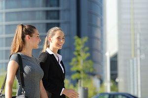 Businesswomen walking and talking in the street.jpg