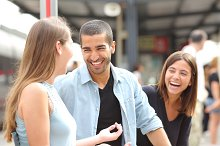 Three friends talking and laughing in a train station.jpg