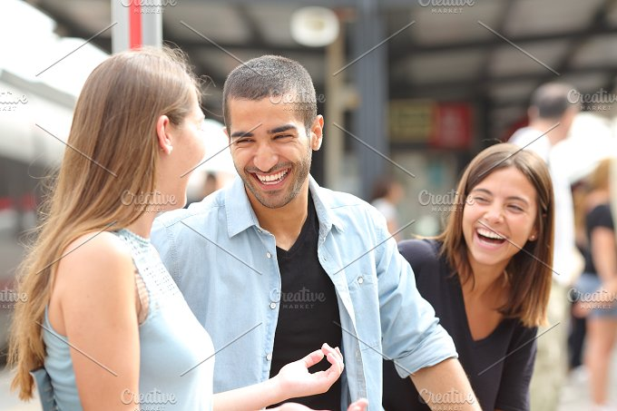 Three friends talking and laughing in a train station.jpg - People