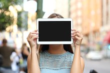 Showing a blank tablet screen covering her face.jpg