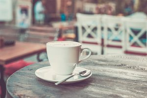 Cappuccino on old dark wooden table