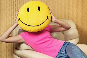 Girl and smiley cushion.