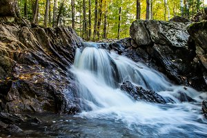 Waterfall inside forest with boots