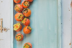 Persimmons on blue wooden tray