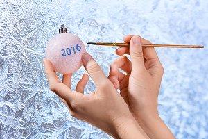 hands drawing on Christmas ball
