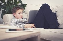Kid watching a movie on his laptop