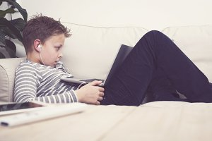 Boy watching a movie on a laptop