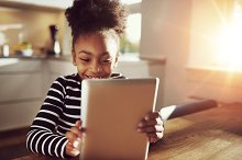 Girl using a tablet and smiling