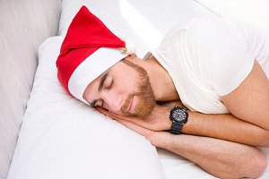 Man with santa hat sleeping in bed
