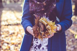 Girl holding autumn fall leaves