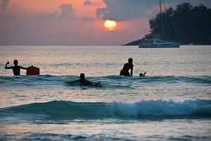 Boys surfing on boards in ocean