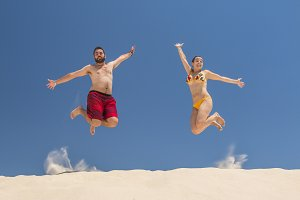 Couple jumping at the beach