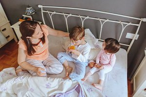 Children having breakfast over a bed