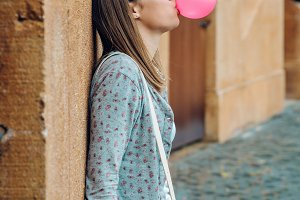 Young girl blowing pink bubble gum