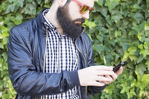 Bearded man uses the smartphone