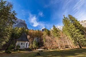 Chapel in the forest under mountains