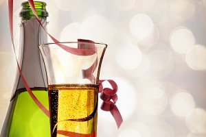Glass and bottle of sparkling white wine and ribbons hanging.jpg