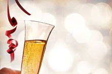 Hand holding a glass of sparkling white wine and ribbons.jpg