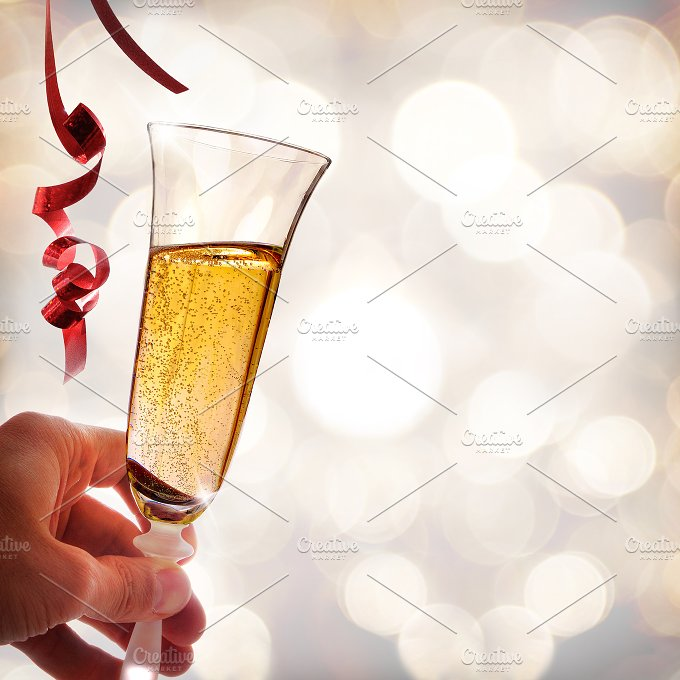 Hand holding a glass of sparkling white wine and ribbons.jpg - Food & Drink