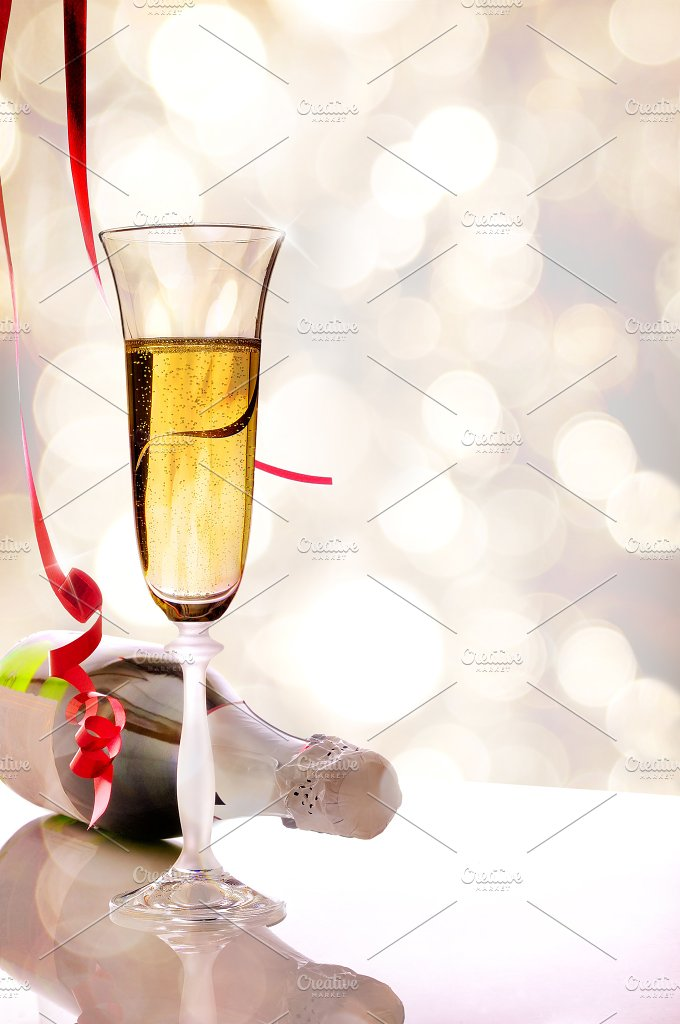 Glass of sparkling white wine and bottle on table vertical.jpg - Food & Drink