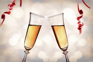 Two glasses of sparkling white wine toasting bokeh background.jpg