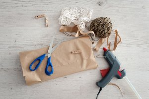 Gift wrapping with boxes and scissors over wooden table