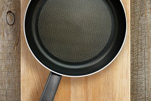 Frying pan on wooden chopping board