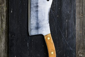 Old meat cleaver on cutting board