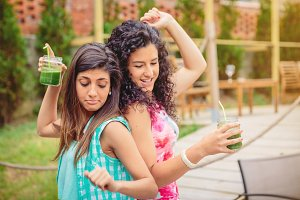 Young women with drinks dancing
