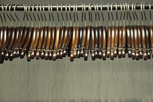 Dark wooden hangers on a rack