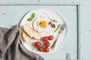 Fried egg, bread slices and tomatoes