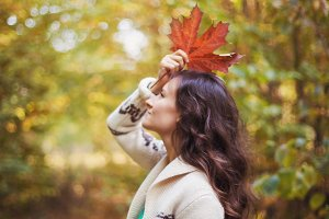 woman holding colorful autumn leaves
