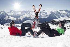 Skiers lying on snow in mountain