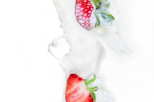 Strawberry falling into milk splash
