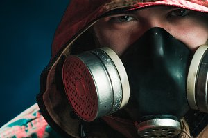 A man in a gas mask on a black backg