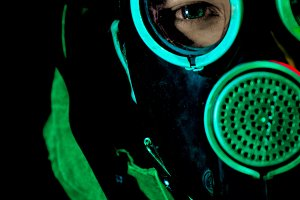 A man in a gas mask on a black backg