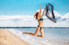 Jumping happy girl on the beach,