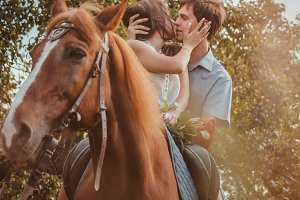 Young beautiful couple  with a horse