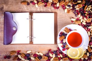 Dried fruits, cup of tea, notebook