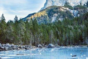 Frozen forest lake in Bavarian Alps