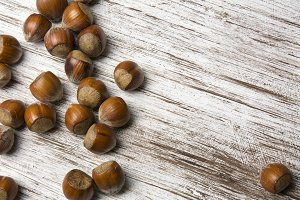 several scattered hazelnuts,  on a w