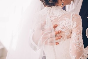 Groom hand on brides dress