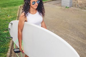 Woman with top holding surfboard