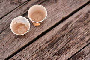 Two Paper Coffee Cups on Wood Deck