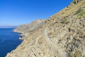 Trail on steep hillside above sea