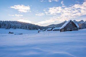 Wooden cottages in winter landscape