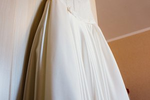 white wedding gown hanging from door