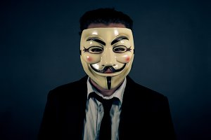 Man in Suit Wearing Anonymous Mask